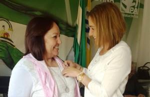 Mª del Carmen Beltrán imponiendo el lazo morado a las asistentes